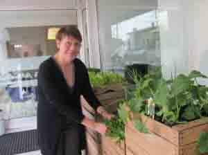 Patrizia Galessi cura l'orto in cassette fuori dal ristorante.
