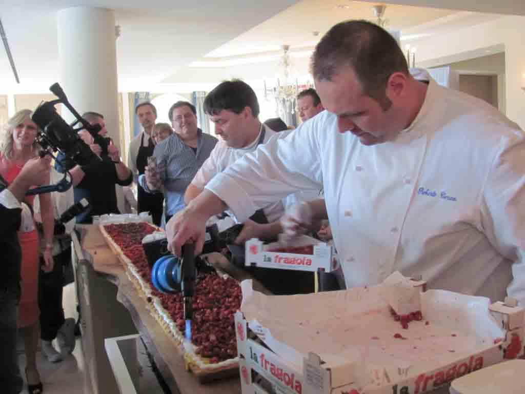 Lo chef Roberto Cerea impegnato a completare in diretta la torta per i fruttivendoli Ascom.